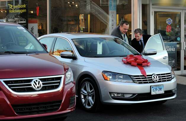 Riverbank Volkswagen sales consultant Frank Grant shows Howard Mansdorf of Fairfield the finer points of his new 2013 Passat TDI SEL at the dealership in Stamford, Conn. on Wednesday, Dec. 5, 2012. The area has seen an increased car sales after damage to vehicles from the effects of Hurricane Sandy. Photo: Cathy Zuraw / Stamford Advocate