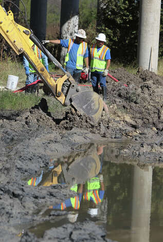San Antonio Water System workers direct heavy equipment at the scene of a sewage spill Wednesday December 5, 2012 near Wurzbach Parkway and Weidner road. SAWS reported that about 63,000 gallons of sewage leaked from a 15 inch pipe in the area and that they are working to clean up the spill. Photo: JOHN DAVENPORT, San Antonio Express-News / ©San Antonio Express-News/Photo Can Be Sold to the Public