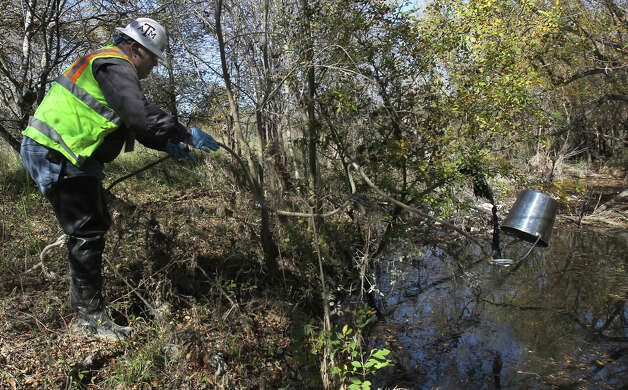 An environmental protection specialist for San Antonio Water System gets ready to test water at a sewage spill. Photo: John Davenport, San Antonio Express-News / ©San Antonio Express-News/Photo Can Be Sold to the Public