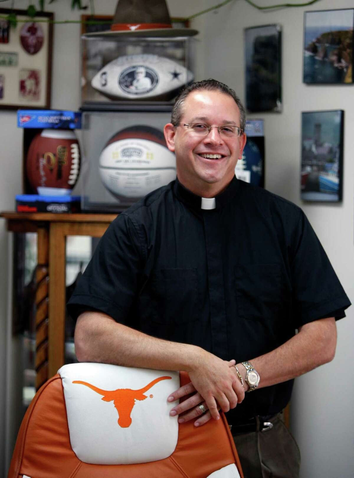Father Eric Ritter displays some of the sports memorabilia in his office at St. Dominic Catholic Church.