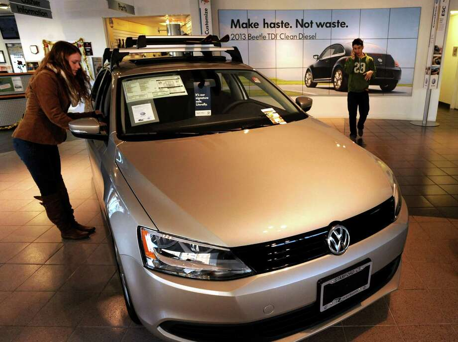 Hannah Hilton looks around the showroom while waiting for her friend's car to be serviced at the Riverbank Volkswagen dealership in Stamford, Conn. on Wednesday, Dec. 5, 2012. The area has seen an increased car sales after damage to vehicles from the effects of Hurricane Sandy. Photo: Cathy Zuraw / Stamford Advocate
