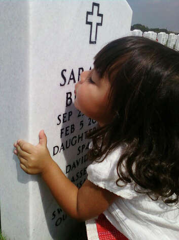 Wendy-Rae Guerrero, Sarah Brasse's half-sister, kisses her siblings' headstone. The photo was taken a year after Sarah's death when Guerrero was two years old. CPS investigation