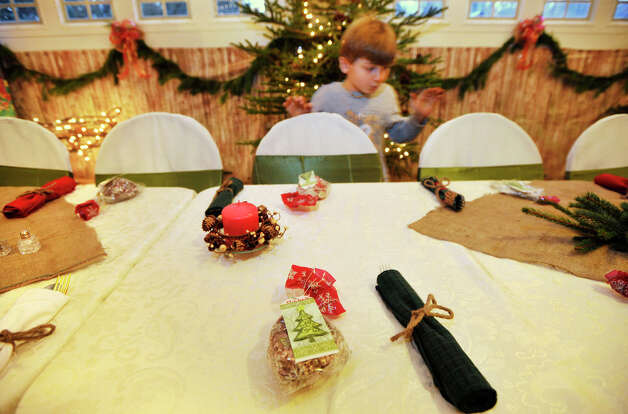 Kristopher DellaSorte, 9, goes around the table looking at everyone's Christmas ornament party favor in his family's garage, which has been transformed into a Christmas-themed dining room. Photographed on Wednesday, Dec. 5, 2012. Photo: Jason Rearick / The News-Times