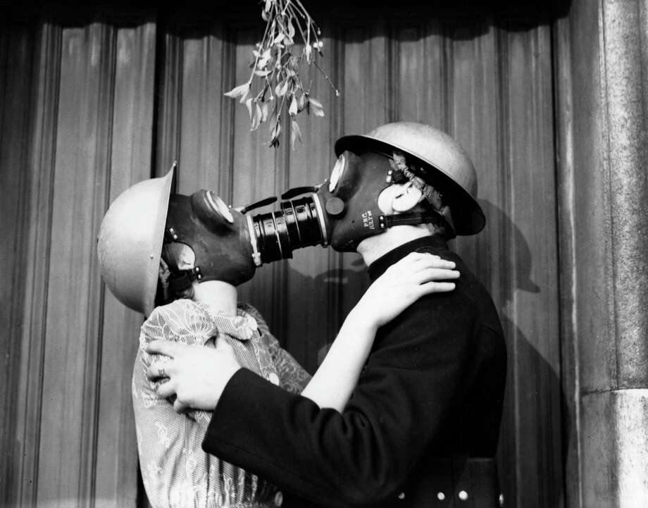 A couple kissing under the mistletoe, wearing gas masks.   (Photo by Fox Photos/Getty Images) Photo: Fox Photos, Stringer / Hulton Archive