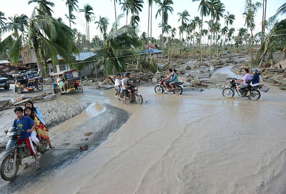 Motorists traverse a flooded road in New Bataan town in Compostela Valley province after the powerful Typhoon Bopha laid waste to the area. Photo: Ted Aljibe, AFP/Getty Images