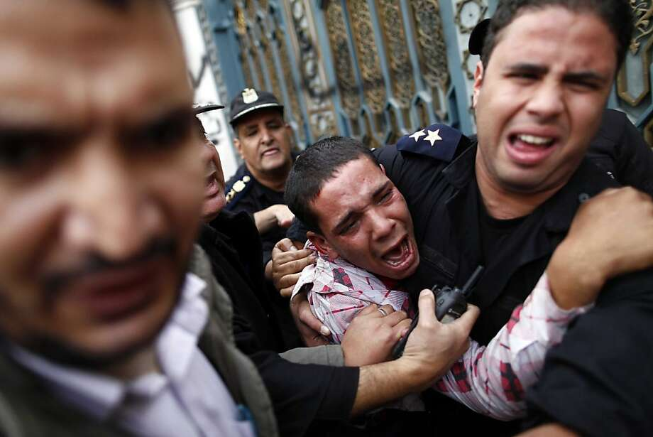 Egyptian police protect an opposition demonstrator after a scuffle with members of the Muslim Brotherhood in clashes outside the presidential palace. Photo: Mahmoud Khaled, AFP/Getty Images