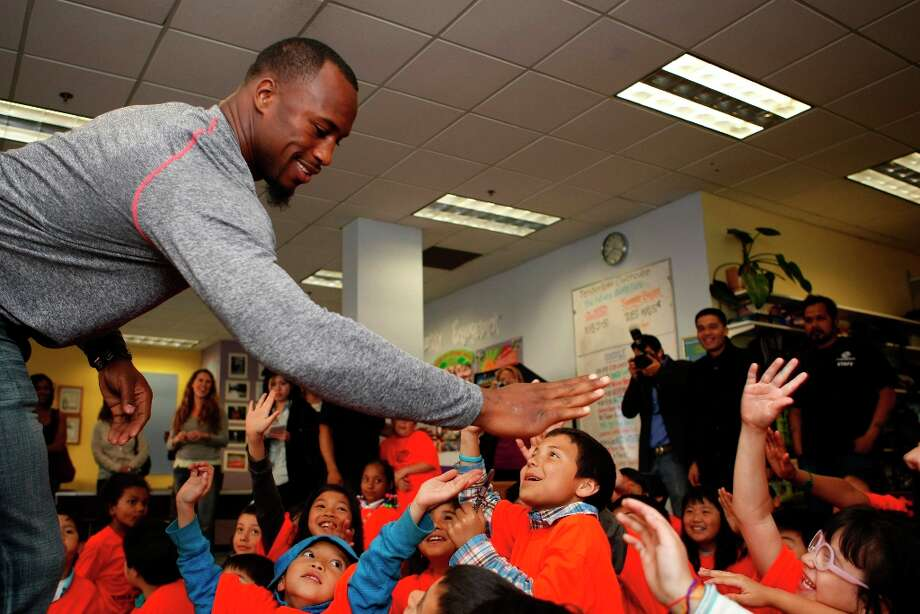 Vernon Davis of the San Francisco 49ers gives high fives to children at the Tenderloin Boys and Girls Clubhouse in San Francisco Calif, on Friday, May 20, 2011. Photo: Alex Washburn, The Chronicle / SFC