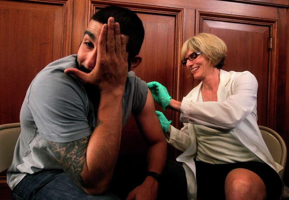Romo can't watch Dr. Susan Fernyak innoculate him with the whooping cough vaccine. Photo: Paul Chinn, The Chronicle / SFC