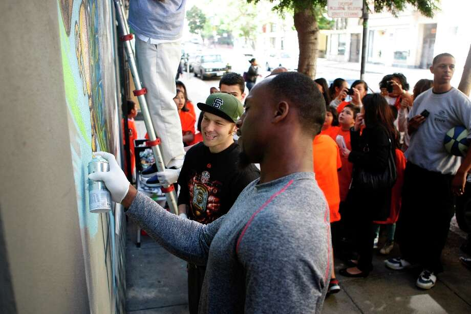 Vernon Davis of the 49ers helps paint a mural created by Cameron Moberg at the Tenderloin Boys and Girls Clubhouse. Photo: Alex Washburn, The Chronicle / SFC