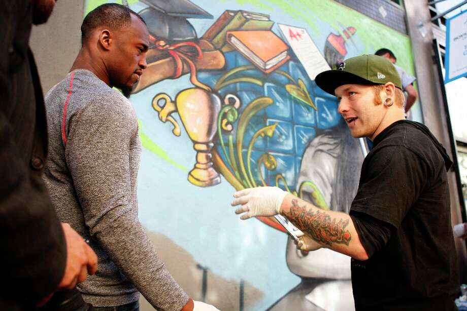 Vernon Davis, who was a studio art major at Maryland, talks to Cameron Moberg in front of the mural that Moberg has designed for the Tenderloin Boys and Girls Club. Photo: Alex Washburn, The Chronicle / SFC