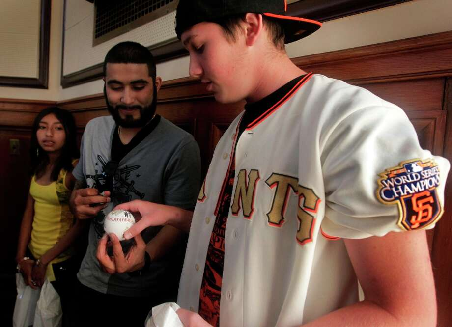 Giants relief pitcher Sergio Romo autographs a baseball for Lucas Selig after the high school senior got his whooping cough innoculation in San Francisco, Calif. on Tuesday, August 2, 2011. Romo visited the Department of Public Health to encourage students to get their whooping cough immunization which is now required for all secondary school students. Photo: Paul Chinn, The Chronicle / SFC