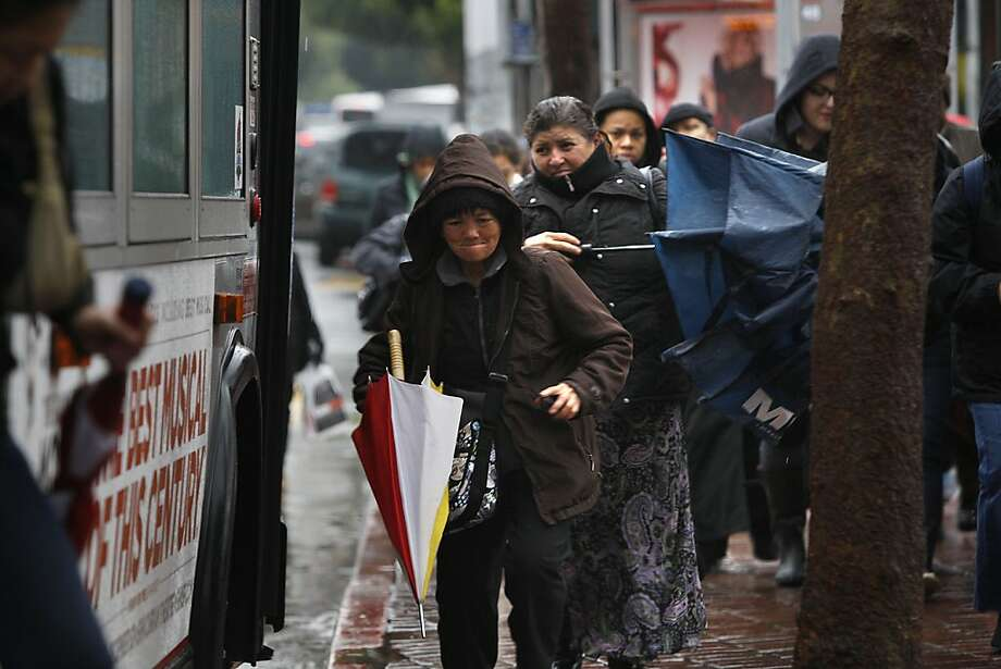 Commuters at 24th and Mission streets in San Francisco cope with the latest in a series of storms. Forecasters say we can put away our umbrellas for at least 10 days, but no clouds means cooler nights. Photo: Liz Hafalia, The Chronicle