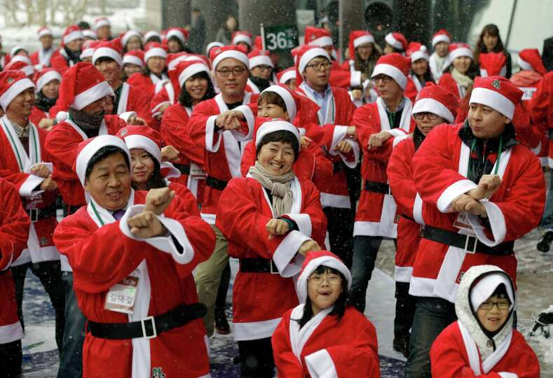 Volunteer workers, dressed in Santa Claus costumes, perform South Korean rapper PSY's