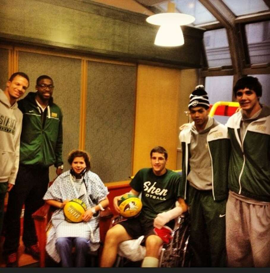 Bailey Wind, 17, and Matt Hardy, 17, seated, were visited by O.D. Anosike, second from left, and other members of the Siena men's basketball team on Wednesday. The players visited Wind and Hardy at Albany Medical Center Hospital where the teens were being treated for injuries they suffered in a Saturday night vehicle crash on the Northway. Anosike posted the photograph on Twitter.