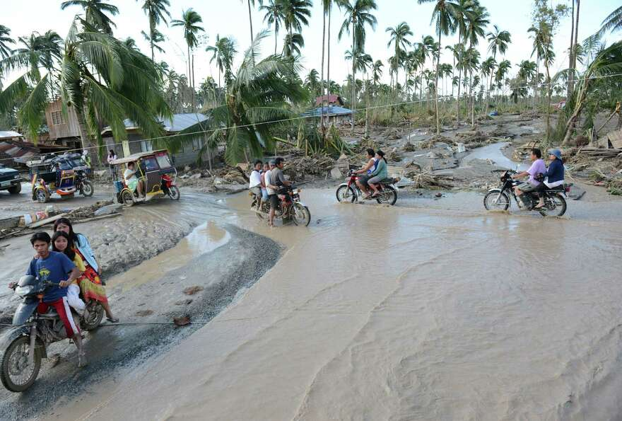 Motorists traverse a flooded road in New Bataan town, Compostela Valley province on December 5, 2012