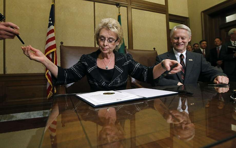 As the secretary of state watches, Washington Gov. Chris Gregoire goes through a stack of pens signing Referendum 74. Photo: Elaine Thompson, Associated Press
