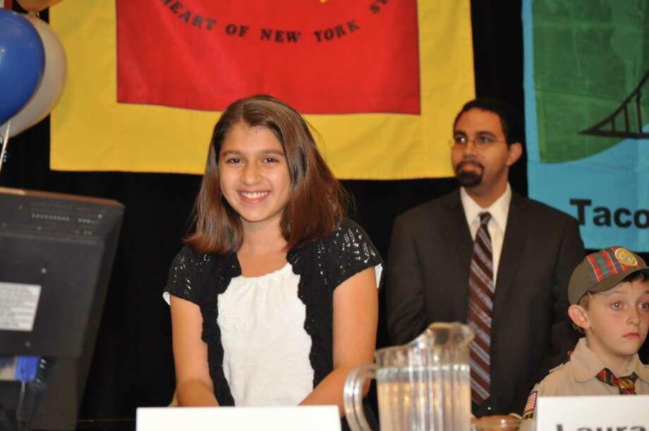 Safia Zaman, a student at E.R. Hughes Elementary School in New Hartford, Oneida County, finishes singing the Star-Spangled Banner to begin the general session of the New York State PTA?s 116th annual convention in Saratoga Springs last month. Looking on is state Education Department Commissioner John King, who delivered the keynote speech on the different initiatives occurring in the state?s educational system. More than 400 delegates, guests and exhibitors gathered together to conduct the business of the organization, attend workshops and elect the next state officers. (Submitted photo)