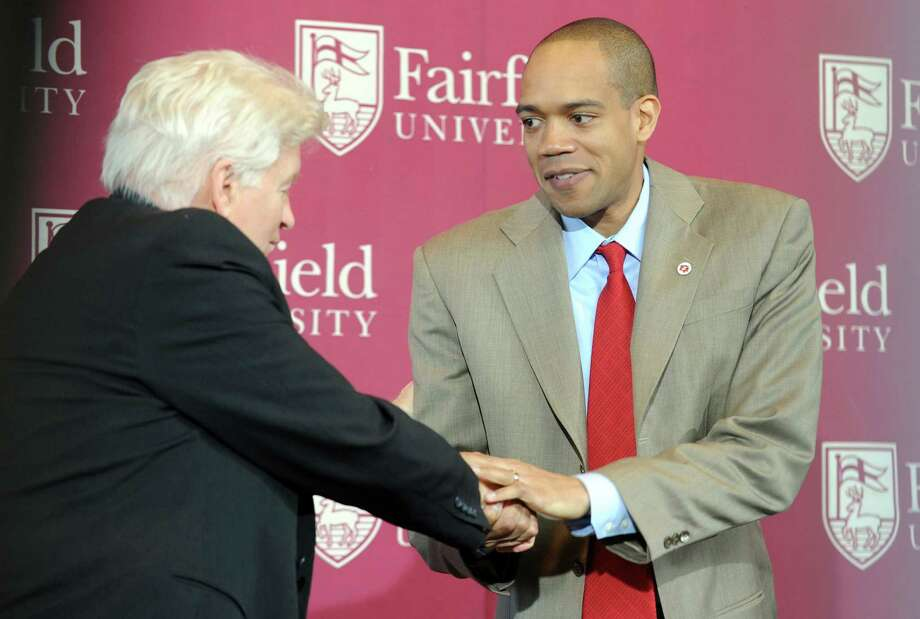 New Fairfield University men's basketball coach Sydney Johnson, right, shakes hands with Eugene Doris, Director of Athletics, Wednesday April 6, 2011 during a press conference at the John Barone Campus Center. Photo: Autumn Driscoll, ST / Connecticut Post