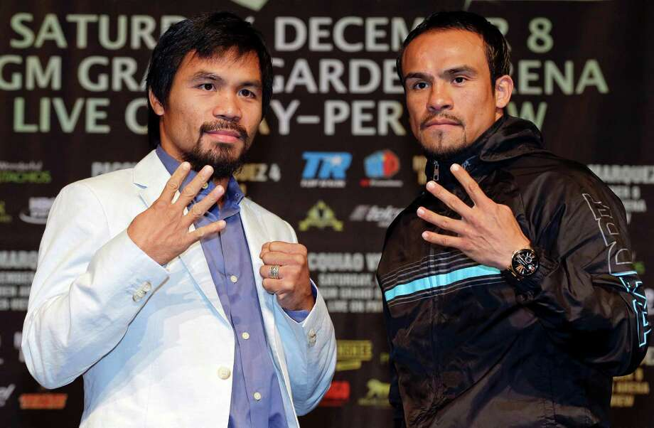 Manny Pacquiao, left, and Juan Manuel Marquez, right, pose for photos during a news conference, Wednesday, Dec. 5, 2012, in Las Vegas. Pacquiao and Marquez are scheduled to face off in a welterweight boxing match on Saturday. (AP Photo/Julie Jacobson) Photo: Julie Jacobson