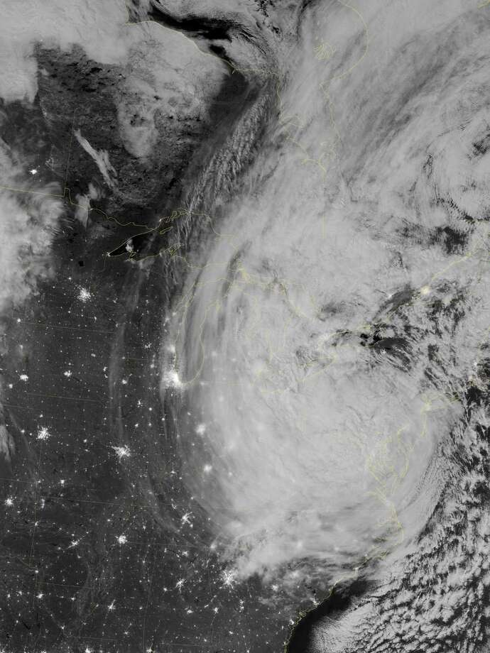 "This image provided by NASA shows the eastern seaboard of the United States of America at night from a composite assembled from data acquired by the Suomi NPP satellite as Hurricane Sandy came ashore on Oct. 30, 2012. The Visible Infrared Imaging Radiometer Suite (VIIRS) on the Suomi NPP satellite acquired this image of hurricane Sandy at 3:35 a.m. EDT. This image is from the ""day-night band"" on VIIRS, which detects light wavelengths from green to near-infrared. The full Moon, which exacerbated the height of the storm water surge, lit the tops of the clouds. Sandy's clouds stretched from the Atlantic Ocean to Chicago. Clusters of lights gave away the locations of some cities throughout the region; but along the East Coast, clouds obscured the lights, many of which were blacked out due to the storm. Several million customers over multiple states were without electricity. Photo: NASA"
