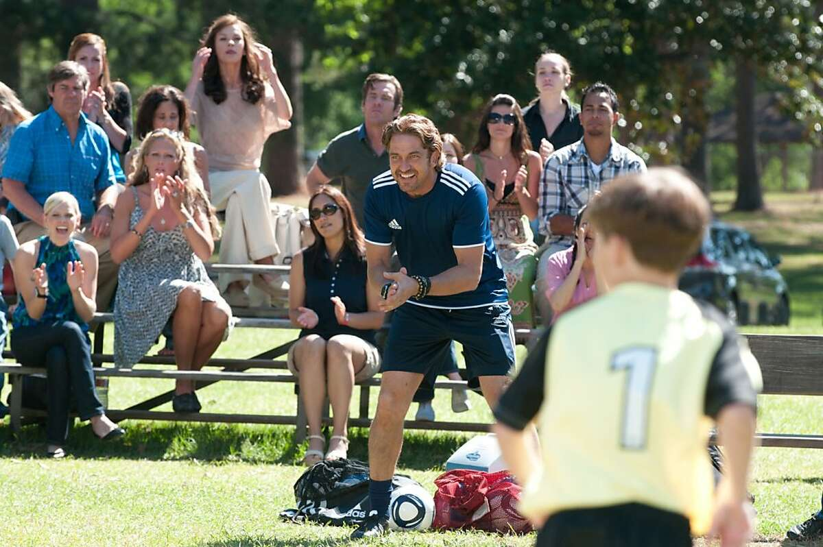 Catherine Zeta-Jones, Dennis Quaid (seated in background) and Gerard Butler (foreground) in PLAYING FOR KEEPS, directed by Gabriele Muccino.
