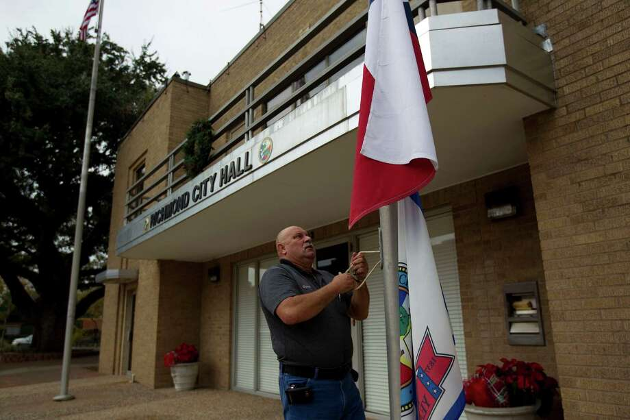 Dennis Koteras, with the City of Richmond Parks Department, places the flags outside of the Richmond City Hall at half staff in response to the death of Hilmar Moore, one of the longest-serving mayors in the United States Wednesday, Dec. 5, 2012, in Richmond. Moore died of natural causes Tuesday at age 92, a family member confirmed. Moore, a fifth-generation Texan, was appointed in September 1949 to fill an unexpired term as mayor of Richmond. H Photo: Johnny Hanson, Houston Chronicle / © 2012  Houston Chronicle