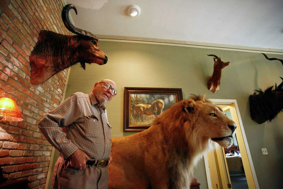 Hilmar Moore stands in his parlor where a few of his trophy animals he shot while on safari are displayed. Photo: Michael Paulsen, Houston Chronicle / Houston Chronicle