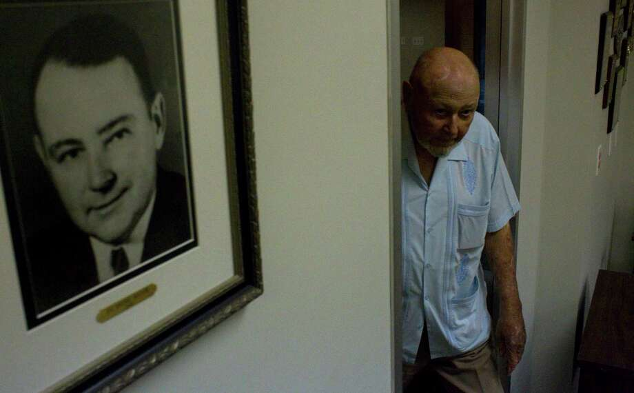 Considered to be the longest-serving mayor, Hilmar Moore, 90, walks into the Richmond City Hall Annex past a picture of himself when he was first took office in 1949 Monday, Aug. 16, 2010, in Richmond. Photo: Johnny Hanson, Houston Chronicle / Houston Chronicle