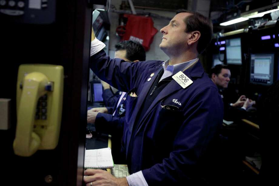 FILE - In this Nov. 15, 2012, file photo, traders work on the floor at the New York Stock Exchange, in New York. World stock markets meandered Tuesday, Dec. 4, as traders weighed a surprise drop in U.S. factory production against hopes that the U.S. will avoid the so-called fiscal cliff. (AP Photo/Seth Wenig, File) Photo: Seth Wenig