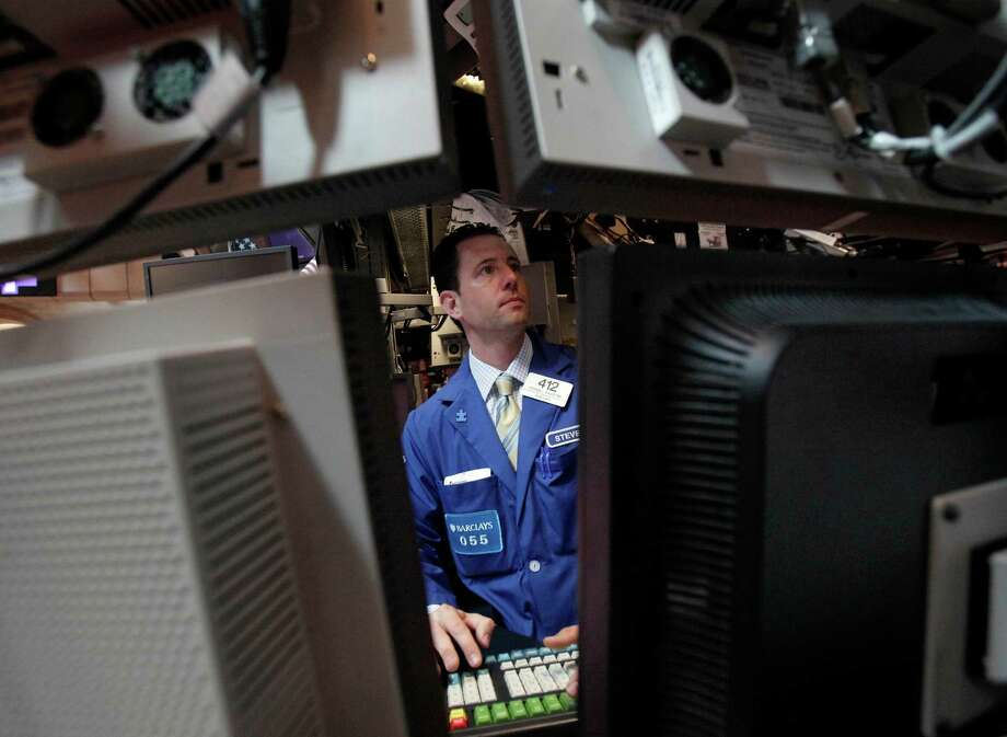 FILE- In this May 17, 2012 file photo specialist Stephen D'Agostino works at his post on the floor of the New York Stock Exchange. (AP Photo/Richard Drew, File) Photo: Richard Drew