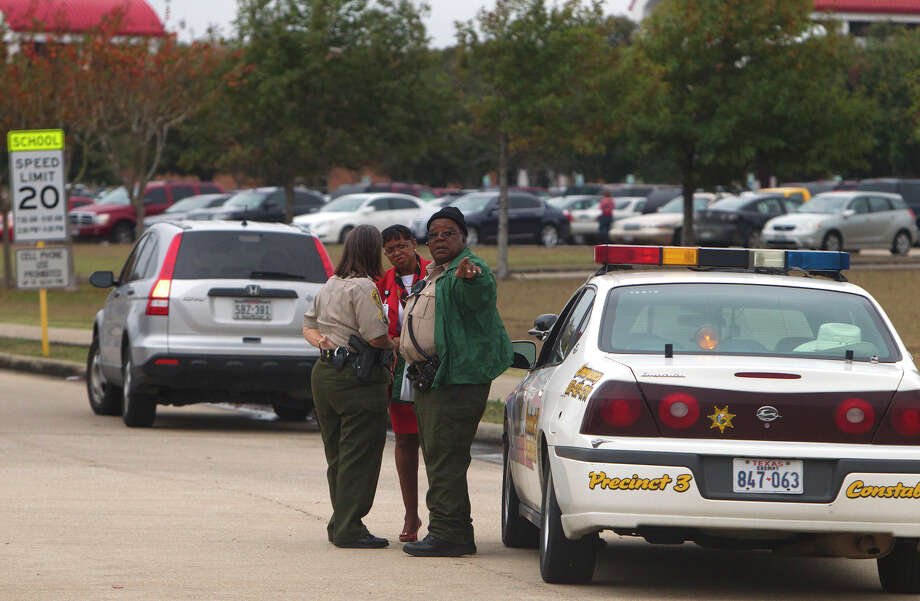 Law officers gather outside North Shore High School, where a 17-year-old student shot himself. Photo: Cody Duty, MBI / Houston Chronicle