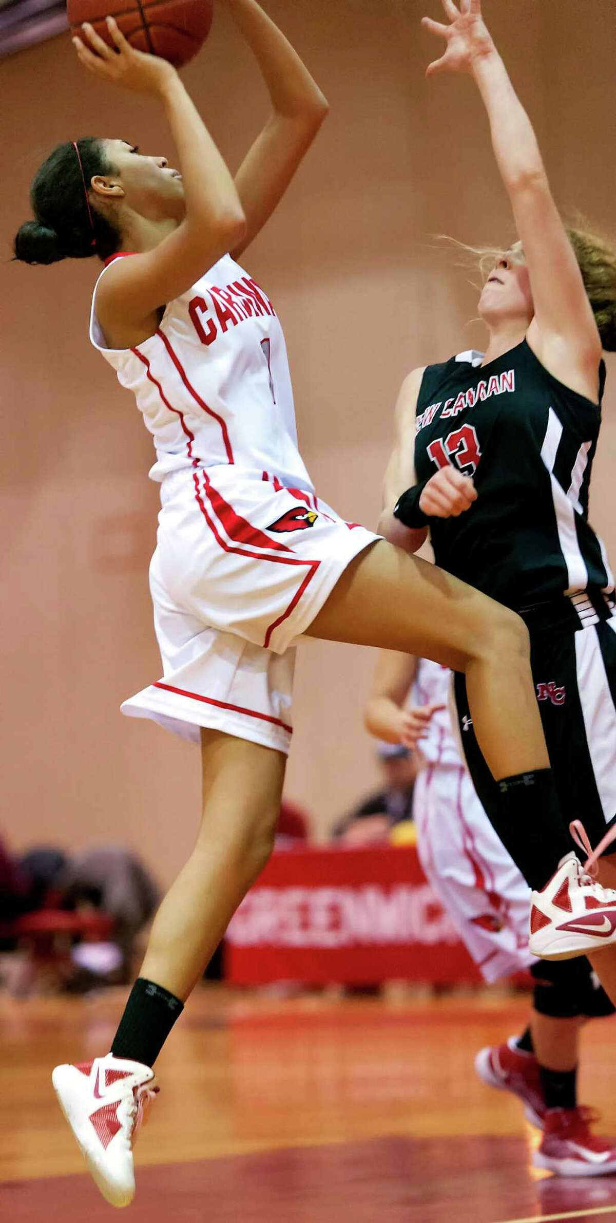 Greenwich high school's Jenny Cespedes goes up for a shot against New Canaan high school's Elizabeth Miller in girls basketball game played at Greenwich high school, Greenwich, CT on Wednesday December 5th, 2012.