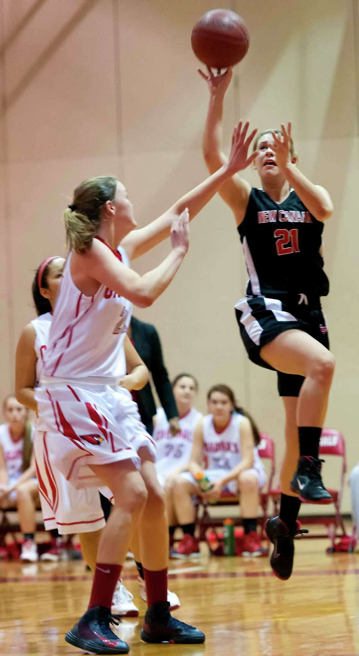 New Canaan high school's Brianna McEwen goes up for a shot in a girls basketball game against Greenwich high school played at Greenwich high school, Greenwich, CT on Wednesday December 5th, 2012. At left is Greenwich high school's Abbie Wollf .