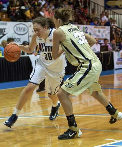 Connecticut forward Breanna Stewart, left, attempts to dribble around Purdue forward Sam Ostarello during an NCAA women's college basketball game in St. Thomas, U.S. Virgin Islands, Saturday, Nov. 24, 2012. Connecticut won 91-57. (AP Photo/Thomas Layer) Photo: Thomas Layer, Associated Press / AP