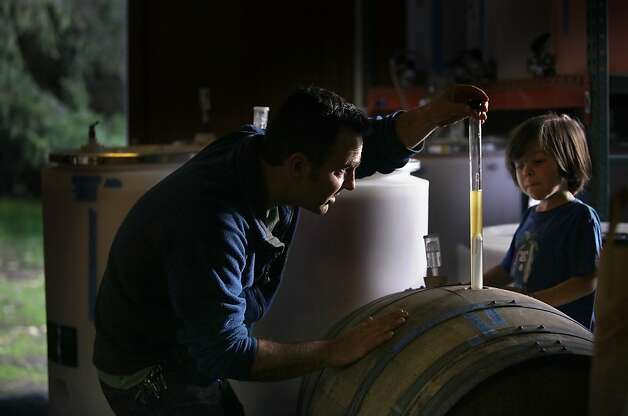 Scott Heath takes a gravity reading of cider fermenting in a barrel while his son, Benny, watches at their cidery in Sebastopol. Photo: Liz Hafalia, The Chronicle