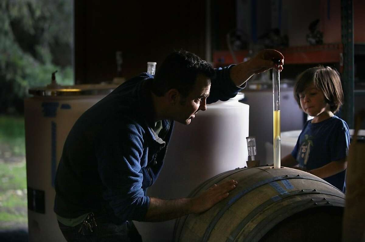 Scott Heath taking a gravity ready of cider fermenting in a barrel while his son Benny Heath, 5 years old, watches at their cidery in Sebastopol, Calif., on Wednesday, November 28, 2012.