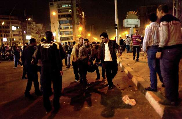 Protesters opposed to Egyptian President Mohammed Morsi evacuate and injured fellow protester during clashes between supporters of president Mohammed Morsi and their rivals in front of the president palace, in Cairo, Egypt, Wednesday, Dec. 5, 2012. Supporters and opponents of Egyptian leader Mohammed Morsi pelted each other with rocks and firebombs and fought with sticks outside the presidential palace in Cairo on Wednesday, as a new round of protests deepened the country's political crisis. (AP Photo/Nasser Nasser) Photo: Nasser Nasser