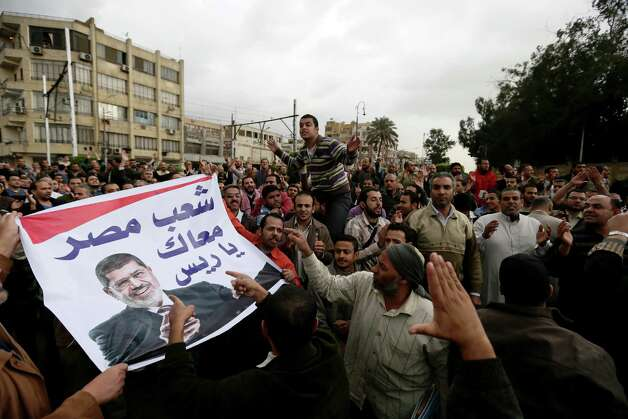 "Supporters of Egyptian President Mohammed Morsi chant slogans during a demonstration outside the presidential palace, in Cairo, Egypt, Wednesday, Dec. 5, 2012. Supporters of Morsi and opponents clashed outside the presidential palace. Wednesday's clashes began when thousands of Islamist supporters of Morsi descended on the area around the palace where some 300 of his opponents were staging a sit-in. Arabic on the banner reads, ""Egypt's people are with you president."" (AP Photo/Hassan Ammar) Photo: Hassan Ammar"