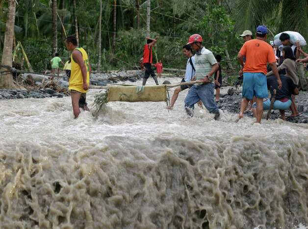 Residents cross a river with the body of a child after retrieving it from the flash flood-hit village of Andap, in New Bataan township, Compostela Valley in southern Philippines Wednesday Dec. 5, 2012, a day after the devastating Typhoon Bopha made landfall. Typhoon Bopha, one of the strongest typhoons to hit the Philippines this year, barreled across the country's south on Tuesday, killing scores of people while triggering landslides, flooding and cutting off power in two entire provinces. (AP Photo/Bullit Marquez) Photo: Bullit Marquez