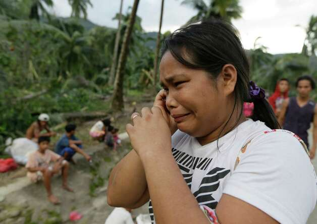 Rosalinda Pasko tearfully breaks the news to a relative of the death of her 2 of her family members at the flash flood-hit village of Andap, New Bataan township, Compostela Valley in southern Philippines Wednesday Dec. 5, 2012. Typhoon Bopha, one of the strongest typhoons to hit the Philippines this year, barreled across the country's south on Tuesday, killing scores of people while triggering landslides, flooding and cutting off power in two entire provinces. (AP Photo/Bullit Marquez) Photo: Bullit Marquez