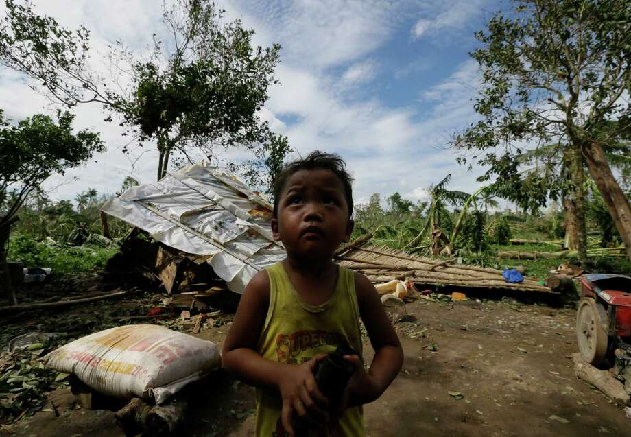 A child stands near his family's damaged house Wednesday Dec. 5, 2012, a day after powerful Typhoon Bopha hit Montevista township Compostela Valley in southern Philippines. Typhoon Bopha, one of the strongest typhoons to hit the Philippines this year, barreled across the country's south on Tuesday, killing scores of people while triggering landslides, flooding and cutting off power in two entire provinces. (AP Photo/Bullit Marquez) Photo: Bullit Marquez