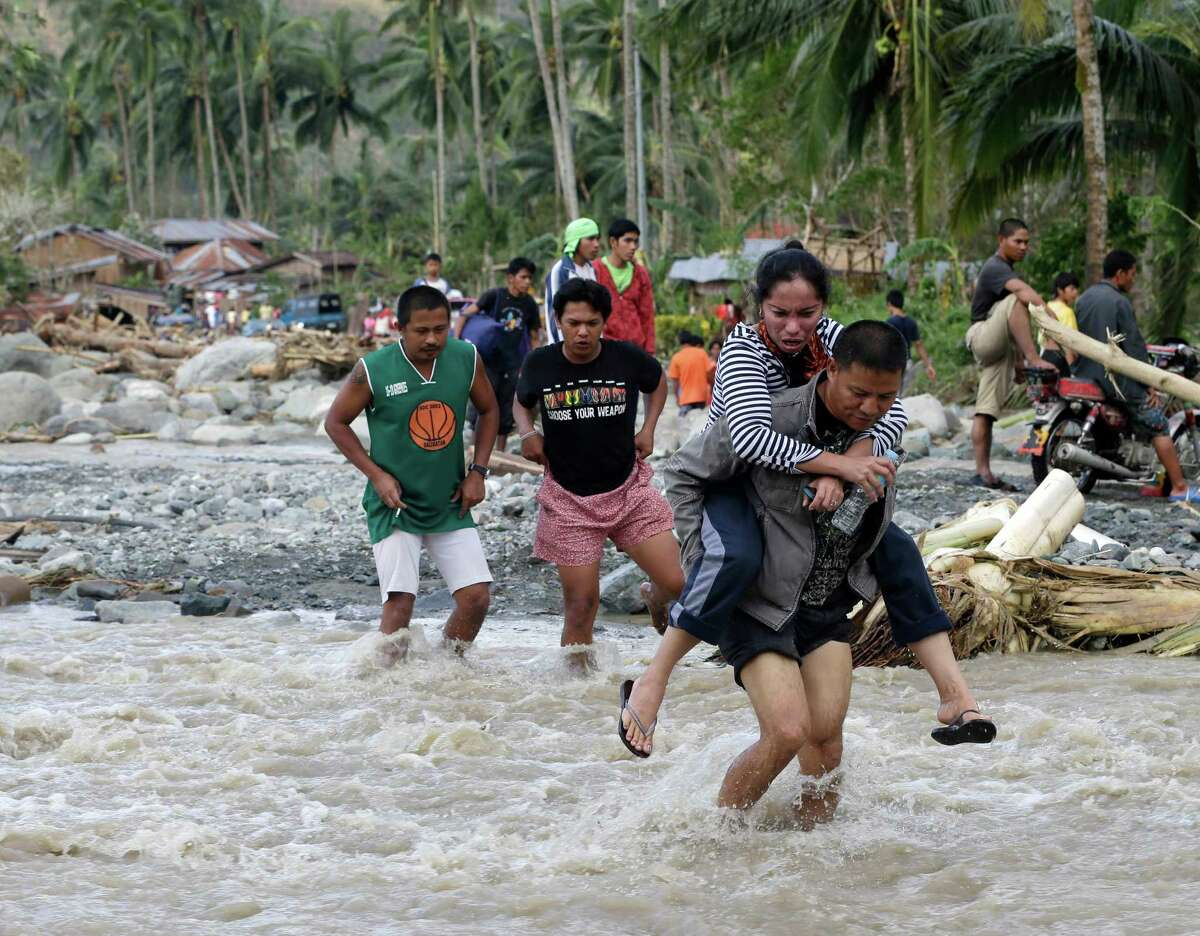 Residents cross a river at the flash flood-hit village of Andap, New Bataan township, Compostela Valley in southern Philippines Wednesday, Dec. 5, 2012. Typhoon Bopha, one of the strongest typhoons to hit the Philippines this year, barreled across the country's south on Tuesday, killing scores of people and forcing more than 50,000 to flee from inundated villages. (AP Photo/Bullit Marquez)