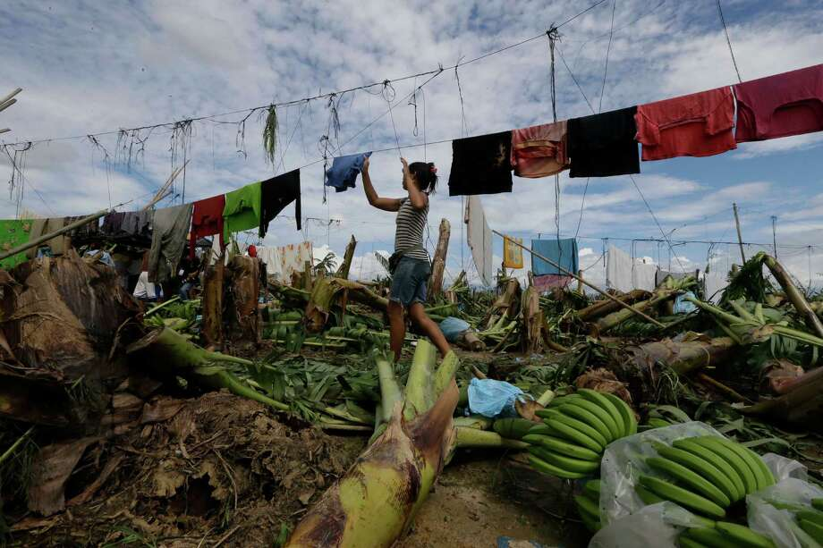 A resident hangs clothing amid fallen trees and debris a day after Typhoon Bopha made landfall in the village of Andap, New Bataan township, Compostela Valley in southern Philippines Wednesday, Dec. 5, 2012. Typhoon Bopha, one of the strongest typhoons to hit the Philippines this year, barreled across the country's south on Tuesday, killing scores of people while triggering landslides, flooding and cutting off power in two entire provinces. (AP Photo/Bullit Marquez) Photo: Bullit Marquez