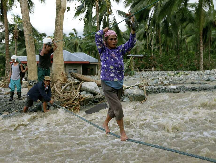 Residents cross a river using suspended ropes at Andap, New Bataan township, Compostela Valley in southern Philippines Wednesday, Dec. 5, 2012, a day after Typhoon Bopha made landfall. Typhoon Bopha, one of the strongest typhoons to hit the Philippines this year, barreled across the country's south on Tuesday, killing scores of people while triggering landslides, flooding and cutting off power in two entire provinces. (AP Photo/Bullit Marquez) Photo: Bullit Marquez