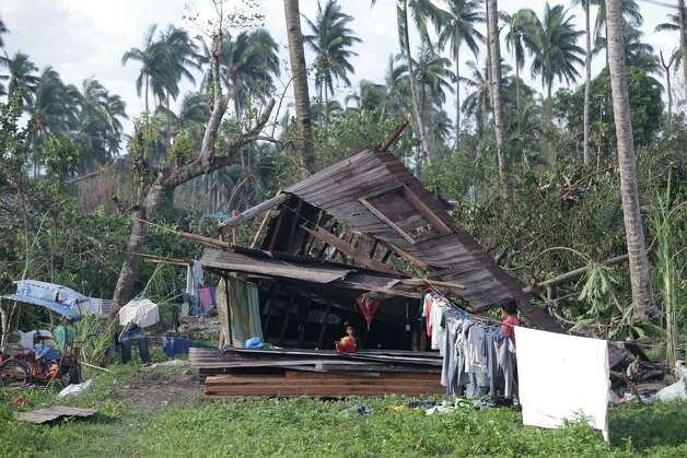 A resident dries their clothes amidst their toppled house at the flash flood-hit village of Andap, New Bataan township, Compostela Valley in southern Philippines Wednesday Dec. 5, 2012. Typhoon Bopha, one of the strongest typhoons to hit the Philippines this year, barreled across the country's south on Tuesday, killing scores of people while triggering landslides, flooding and cutting off power in two entire provinces. (AP Photo/Bullit Marquez) Photo: Bullit Marquez