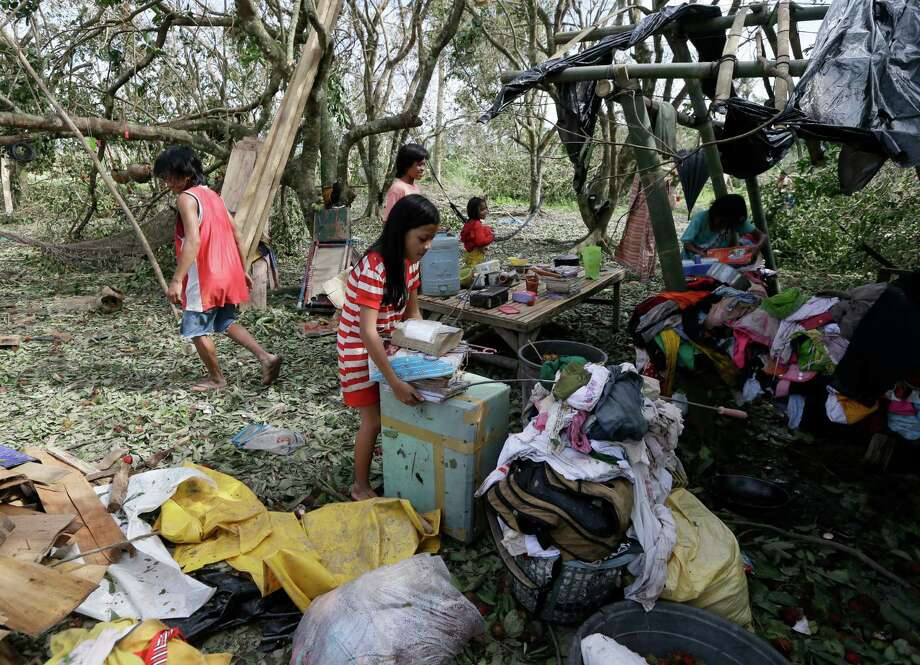 Children retrieve their books and other belongings from their damaged home Wednesday Dec. 5, 2012, a day after powerful Typhoon Bopha hit Montevista township, in the Compostela Valley in southern Philippines. Typhoon Bopha (local name Pablo), one of the strongest typhoons to hit the Philippines this year, barreled across the country's south on Tuesday, killing scores of people and forcing more than 50,000 to flee from inundated villages. (AP Photo/Bullit Marquez) Photo: Bullit Marquez