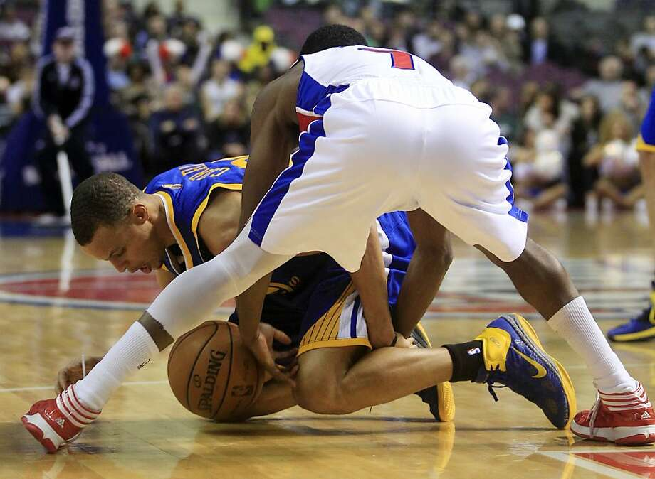 Golden State Warriors guard Stephen Curry and Detroit Pistons guard Brandon Knight (7) battle for a loose ball during the first quarter of an NBA basketball game in Auburn Hills, Mich., Wednesday, Dec. 5, 2012. (AP Photo/Carlos Osorio) Photo: Carlos Osorio, Associated Press