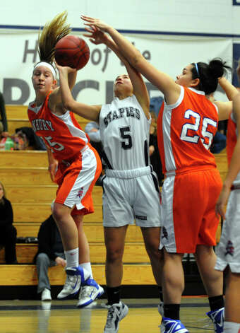 Danbury's #15 Rebecca Gartner, left, and teammate #25 Kayla Handberry, shut down Staples #5 Allison April as she attempts a basket, during girls basketball action in Westport, Conn. on Wednesday December 5, 2012. Photo: Christian Abraham / Connecticut Post