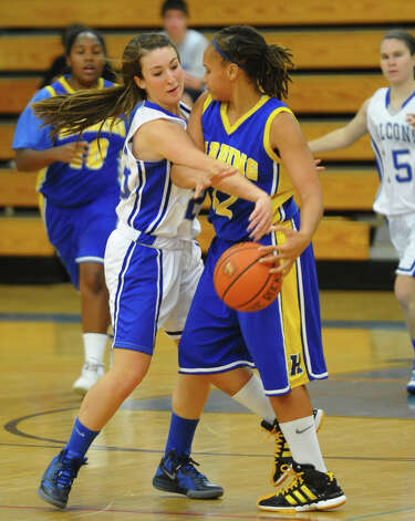 Fairfield Ludlowe's #23 Caroline Pangallo, left, knocks the ball away from Harding's #12 Amber Crawford, during girls basketball action in Fairfield, Conn. on Wednesday December 5, 2012. Photo: Christian Abraham / Connecticut Post