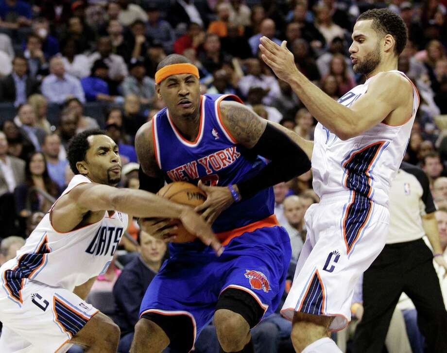 New York Knicks' Carmelo Anthony, center, is fouled as he drives between Charlotte Bobcats' Gerald Henderson, left, and Jeffery Taylor, right, during the second half of an NBA basketball game in Charlotte, N.C., Wednesday, Dec. 5, 2012. The Knicks won 100-98. (AP Photo/Chuck Burton) Photo: Chuck Burton
